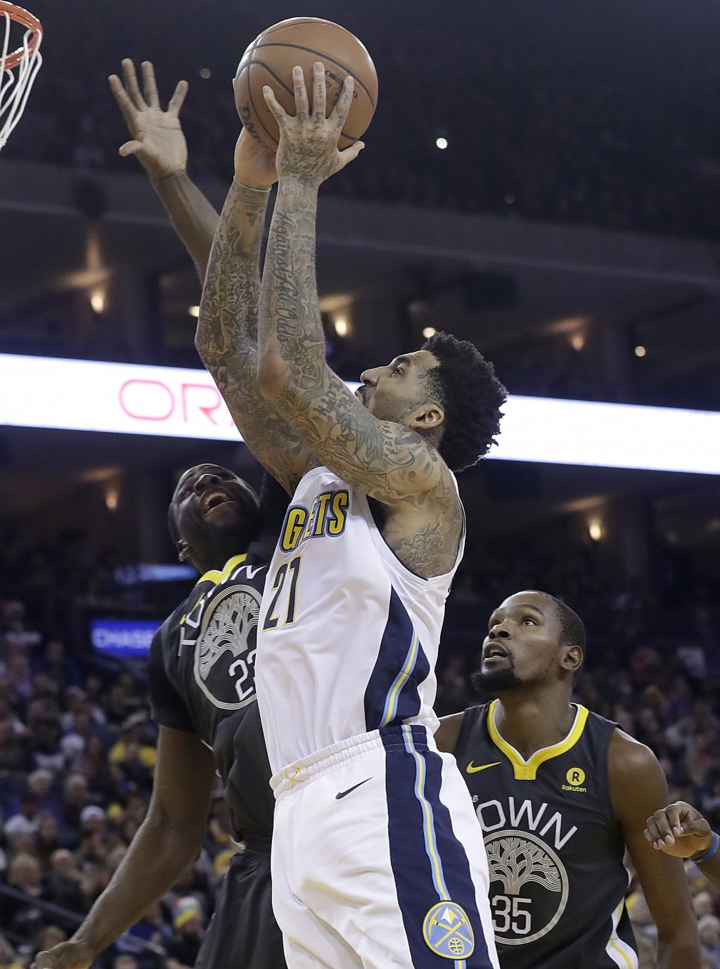 Denver Nuggets forward Wilson Chandler (21) shoots against Golden State Warriors forward Draymond Green (23) and forward Kevin Durant (35) during the ...