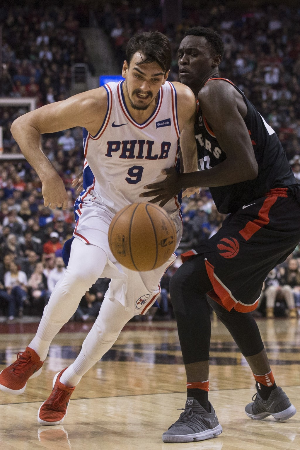 Philadelphia 76ers Dario Saric (left) moves past Toronto Raptors Pascal Siakam during first half NBA basketball action in Toronto on Saturday, Dec. 23...