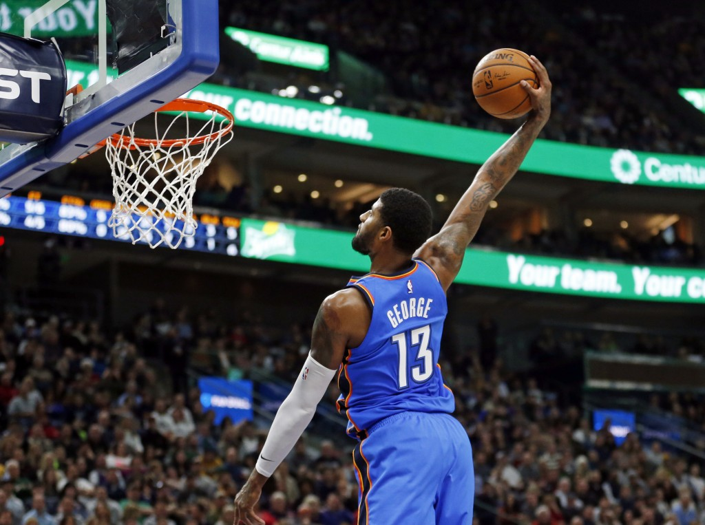 Oklahoma City Thunder forward Paul George (13) dunks against the Utah Jazz in the first half during an NBA basketball game Saturday, Dec. 23, 2017, in...