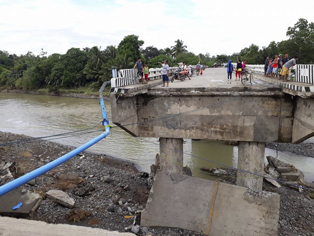 People gather on a bridge which was damaged by the onslaught of the flooding brought about by tropical storm Tembin, Sunday, Dec. 24, 2017 in Zamboang...
