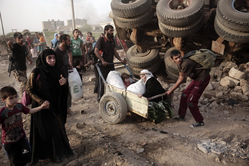 An elderly woman and a child are pulled on a cart as civilians flee heavy fighting between Islamic State militants and Iraqi special forces in western...