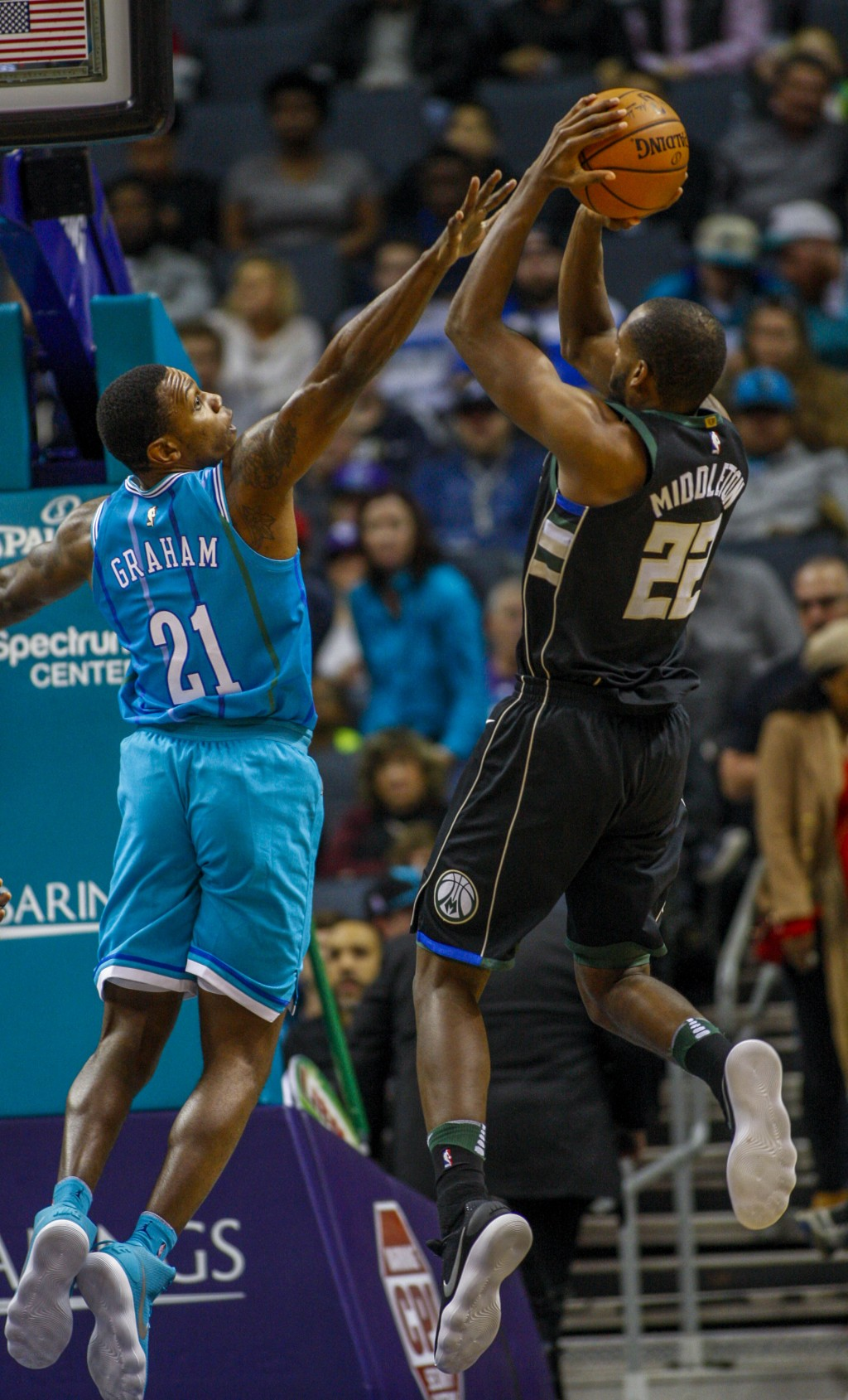 Milwaukee Bucks forward Khris Middleton, right, shoots over Charlotte Hornets guard Treveon Graham in the first half of an NBA basketball game in Char...