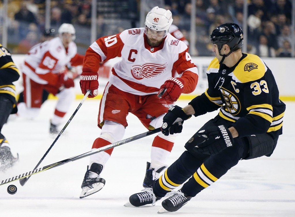 Boston Bruins' Zdeno Chara (33), of Slovakia, battles Detroit Red Wings' Henrik Zetterberg (40), of Sweden, for the puck during the first period of an...
