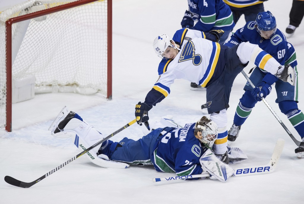 St. Louis Blues' Alexander Steen (20) nearly falls onto Vancouver Canucks goalie Jacob Markstrom, of Sweden, who covers up the puck during the second ...