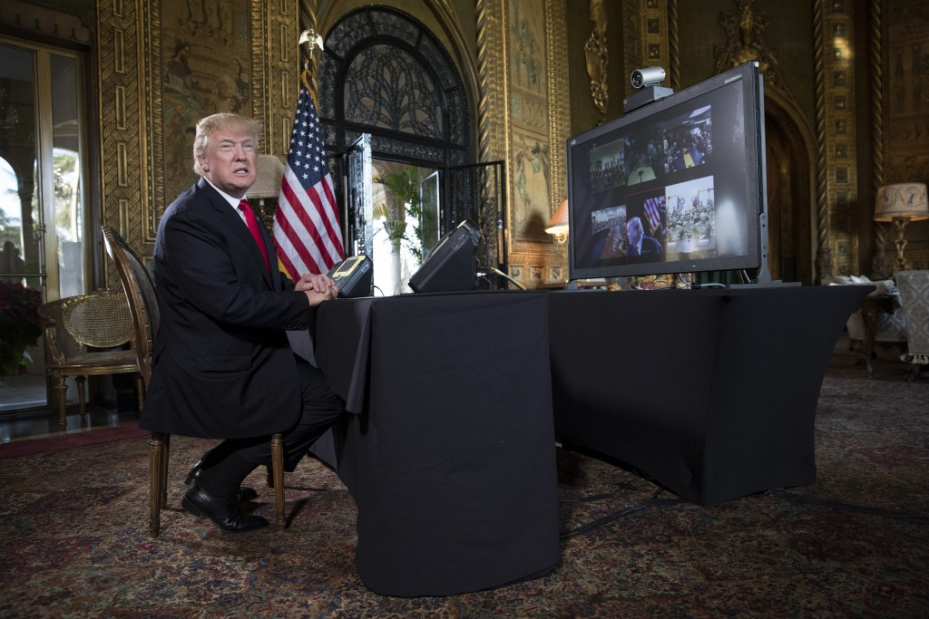 President Donald Trump turns to talk to the gathered media during a Christmas Eve video teleconference with members of the mIlitary at his Mar-a-Lago ...