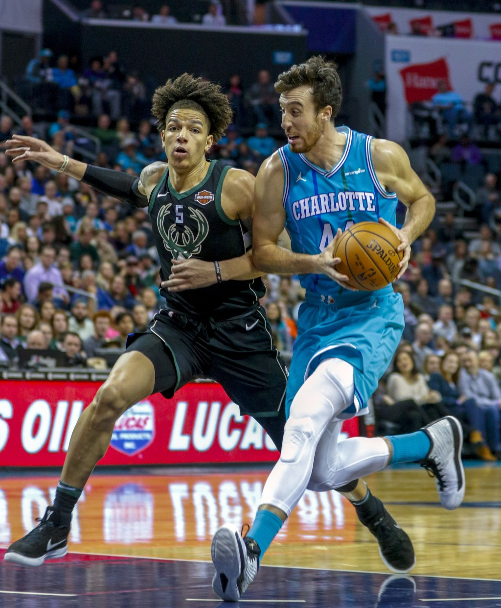 Charlotte Hornets forward Frank Kaminsky, right, drives against Milwaukee Bucks forward D.J. Wilson in the first half of an NBA basketball game in Cha...