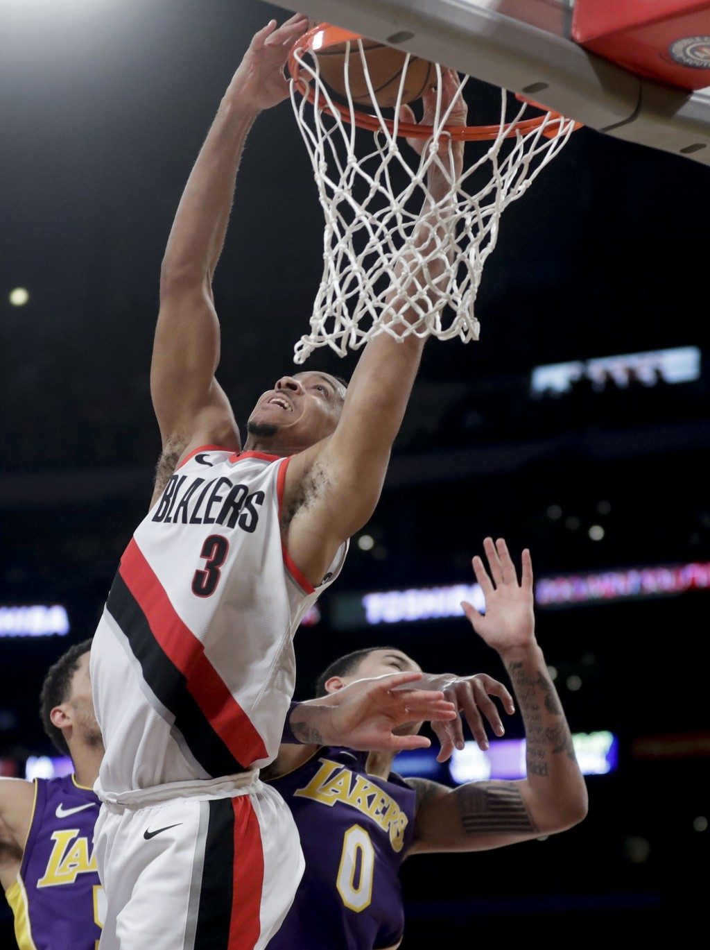Portland Trail Blazers guard CJ McCollum shoots over Los Angeles Lakers forward Kyle Kuzma during the second half of an NBA basketball game in Los Ang...