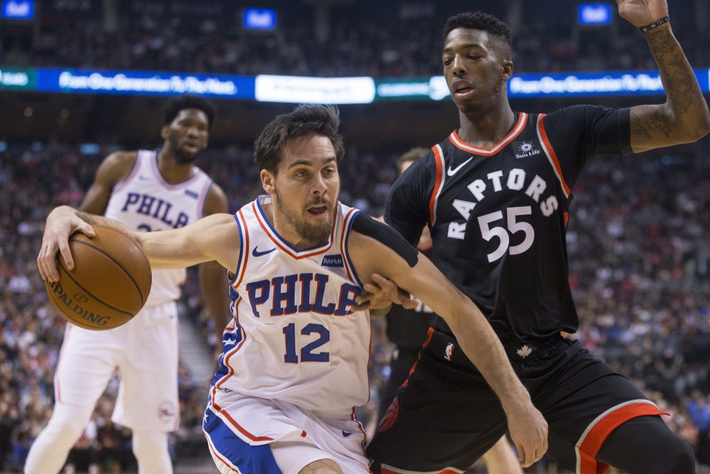 Philadelphia 76ers T.J. McConnell (left) drives at Toronto Raptors' Delon Wright during first half NBA basketball action in Toronto on Saturday, Dec. ...