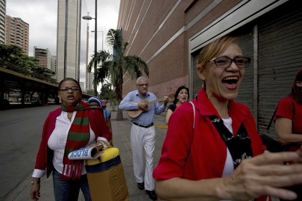 In this Dec. 22, 2017 photo, a Catholic volunteer group plays Venezuelan Christmas carols in downtown Caracas, Venezuela. Inflation is expected to hit...
