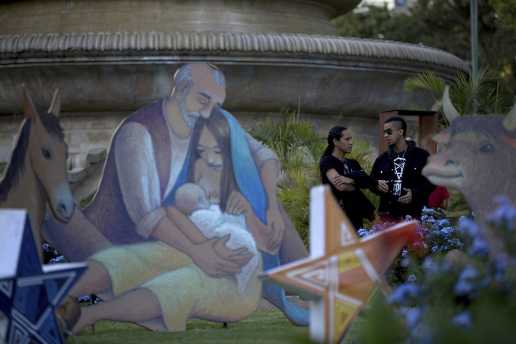 In this photo Dec. 22, 2017 photo, young men chat near a Nativity scene that decorates Altamira square in Caracas, Venezuela. The Christmas lights and...