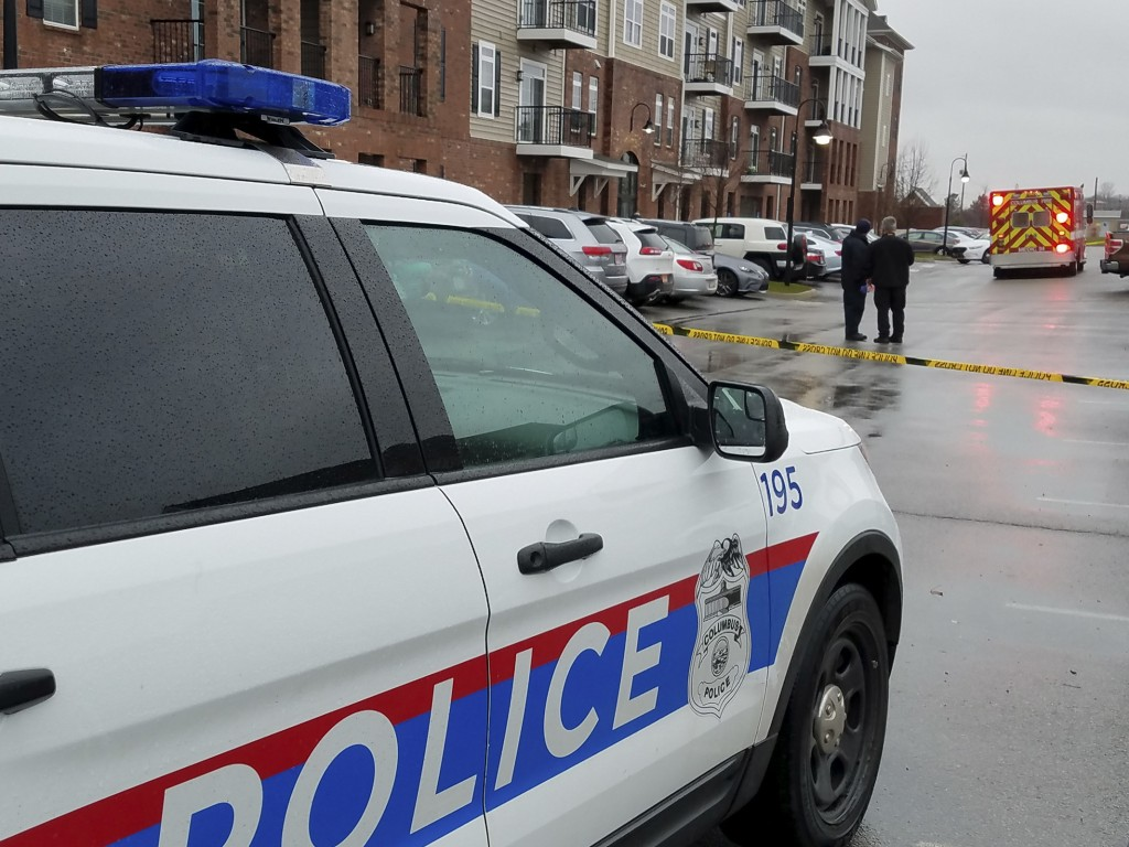 Columbus police investigate the scene where the body of the postmaster, Ginger Ballard, 53, was found lying between two vehicles at an apartment compl...