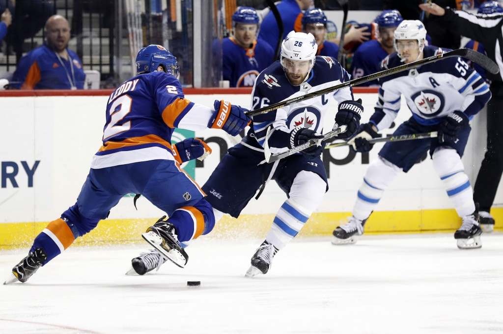 Winnipeg Jets right wing Blake Wheeler (26) battles for the puck with New York Islanders defenseman Nick Leddy (2) in the first period of an NHL hocke...