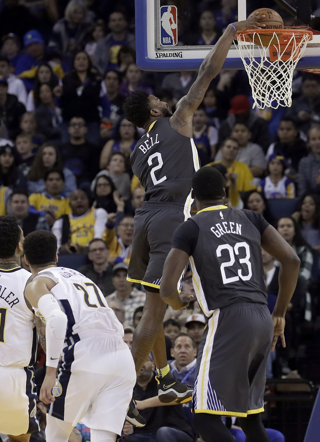 Golden State Warriors forward Jordan Bell (2) dunks against the Denver Nuggets during the first half of an NBA basketball game in Oakland, Calif., Sat...