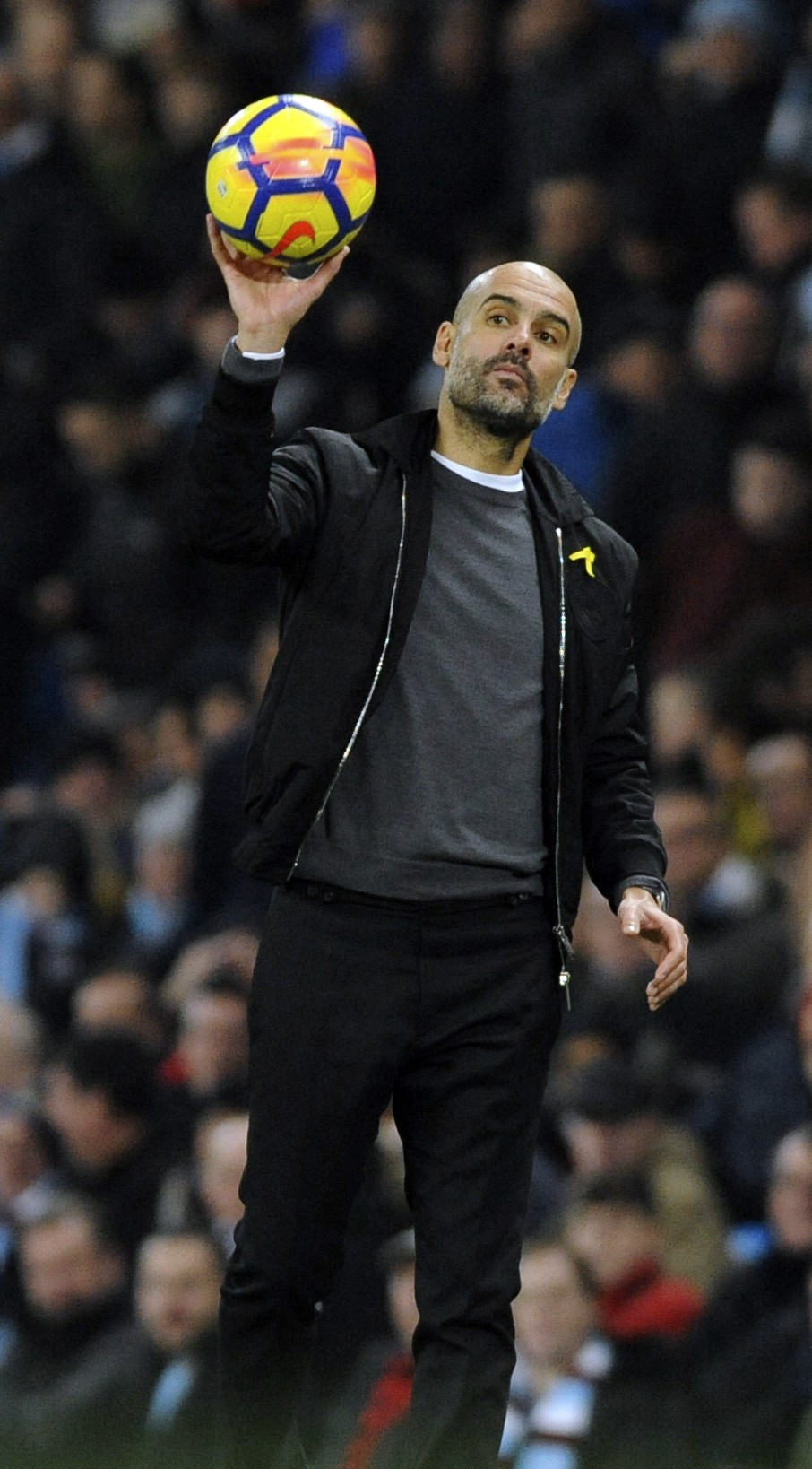 Manchester City manager Josep Guardiola returns the match ball to play during the English Premier League soccer match between Manchester City and Bour...
