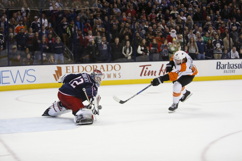 Columbus Blue Jackets' Sergei Bobrovsky, left, of Russia, makes a save against Philadelphia Flyers' Sean Couturier during the shootout period of an NH...