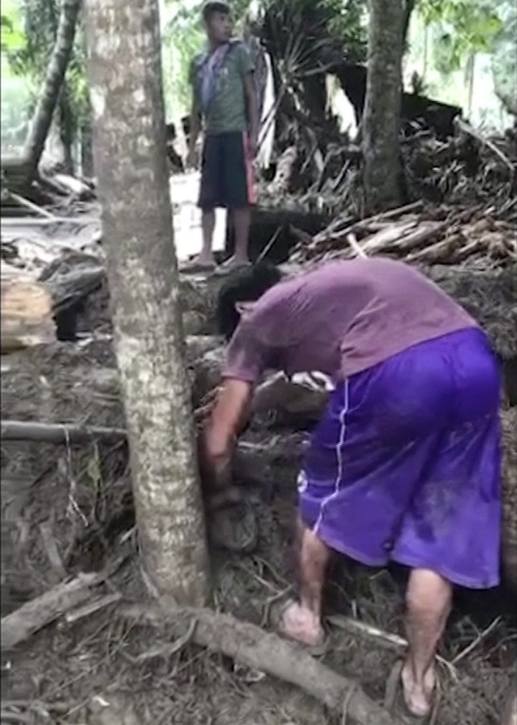 In this image made from video, people search through debris after a flash flood in Lanao del Norte, Mindanao, southern Philippines, Sunday, Dec. 24, 2...