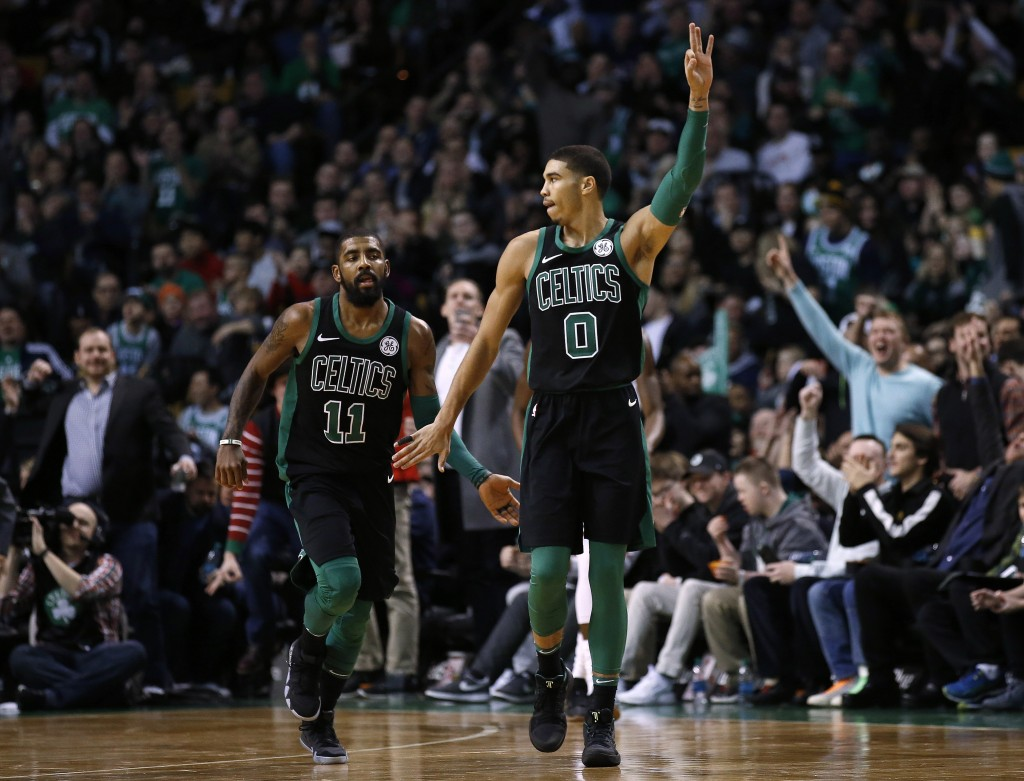 "Boston Celtics' Jayson Tatum (0) signals ""3"" and congratulates teammate Kyrie Irving after Irving hit a 3-point shot during the fourth quarter of Bost..."