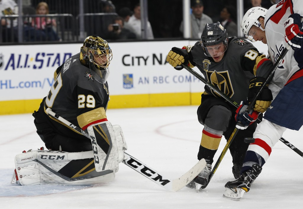 Washington Capitals center Jay Beagle, right, and Vegas Golden Knights defenseman Nate Schmidt (88) vie for the puck after it was blocked by goalie Ma...
