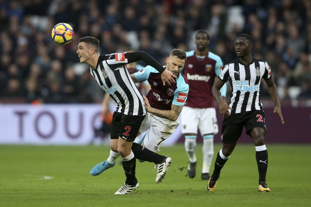 Newcastle United's Ciaran Clark, left, and West Ham United's Marko Arnautovic battle for the ball during the English Premier League soccer match at th...