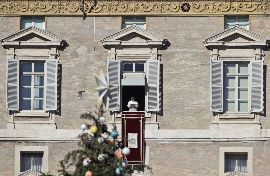 Framed by a Christmas tree, Pope Francis delivers his speech during the Angelus noon prayer from his studio window overlooking St. Peter's Square at t...