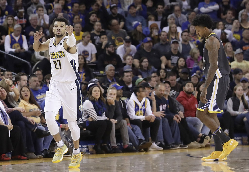 Denver Nuggets guard Jamal Murray (27) celebrates after scoring next to Golden State Warriors guard Nick Young during the second half of an NBA basket...