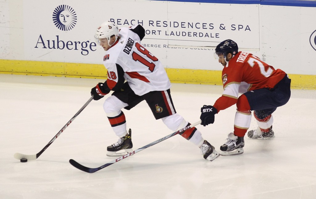 Ottawa Senators' Ryan Dzingel (18) moves the puck as Florida Panthers' Vincent Trocheck, right, defends during the first period of an NHL hockey game,...