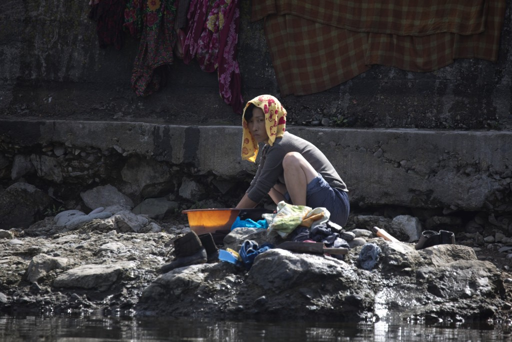 In this Aug. 29, 2017 photo, a North Korean woman washes clothes along the banks of North Korea across from the Chinese border town of Jian in northea...