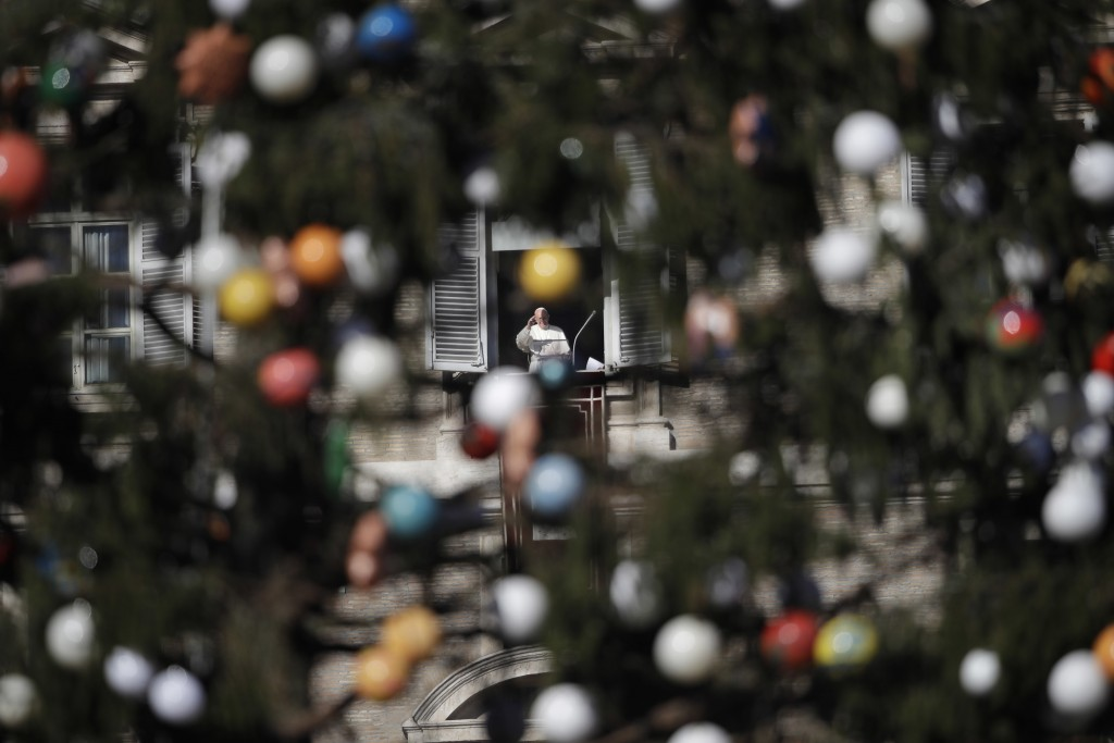 Framed by a Christmas tree, Pope Francis waves to faithful during the Angelus noon prayer he delivered from his studio window overlooking St. Peter's ...