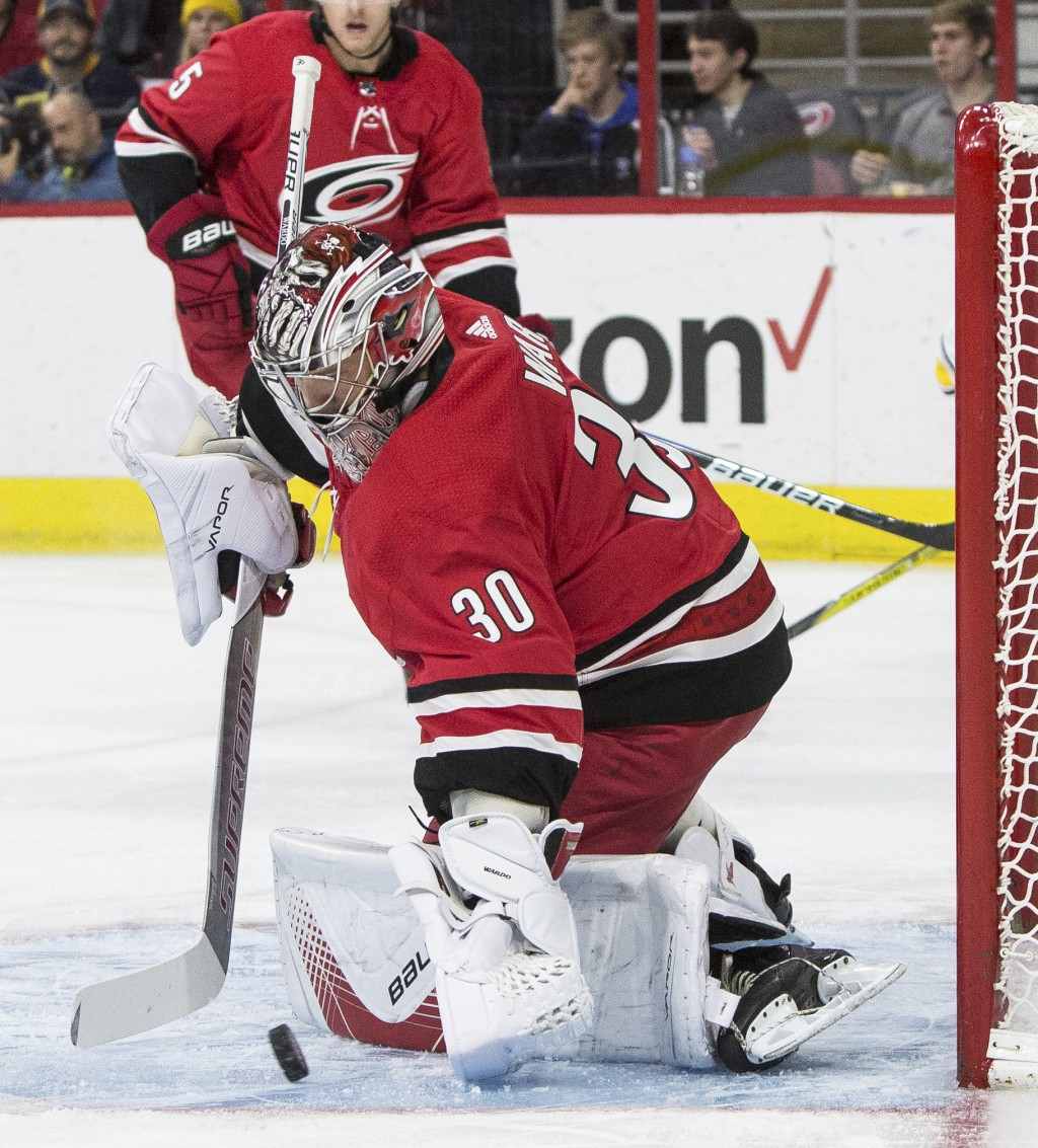 Carolina Hurricanes' goalie Cam Ward (30) makes a save during the first period of an NHL hockey game against the Buffalo Sabres in Raleigh, N.C., Satu...