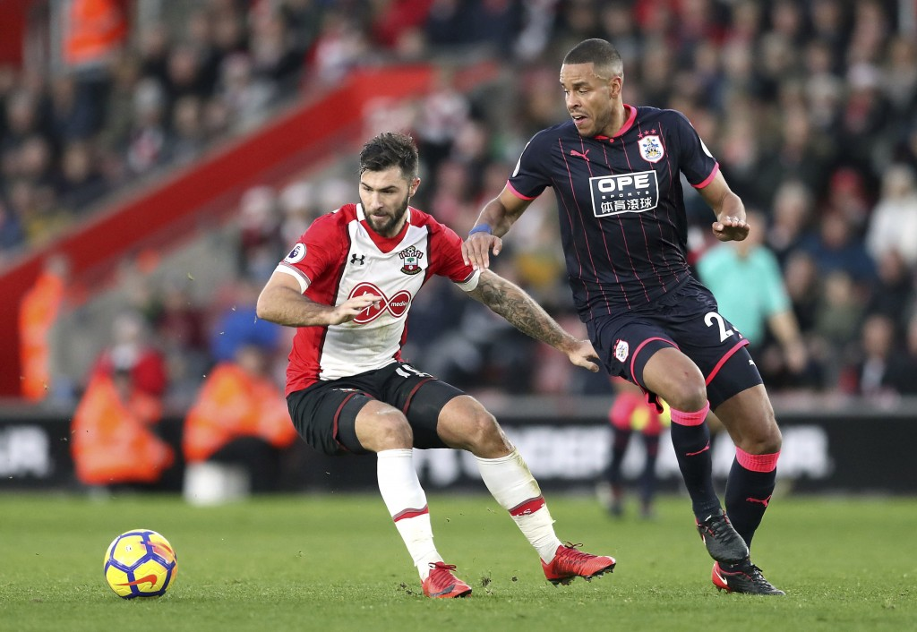 Southampton's Charlie Austin, left and Huddersfield Town's Mathias Jorgensen battle for the ball, during the English Premier League soccer match betwe...