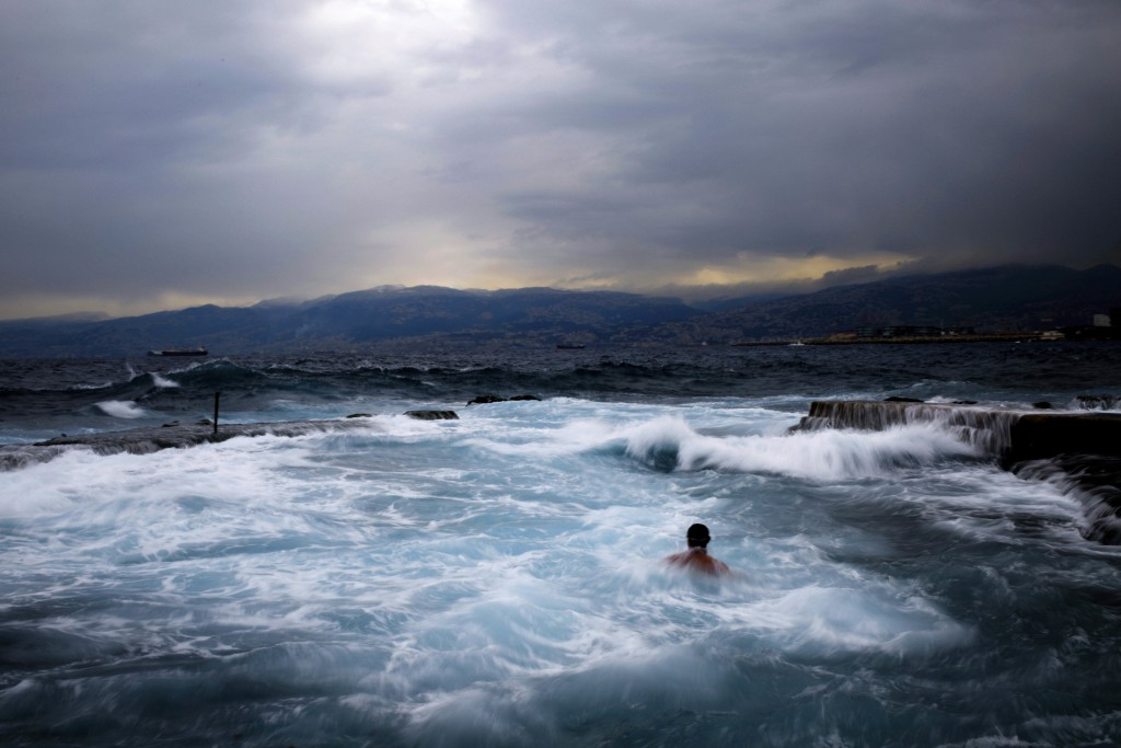 Men swimming during an early morning swim in the Mediterranean sea in cool temperatures of 8 degrees celsius, 46.4 Fahrenheit, across Beirut, Lebanon,...