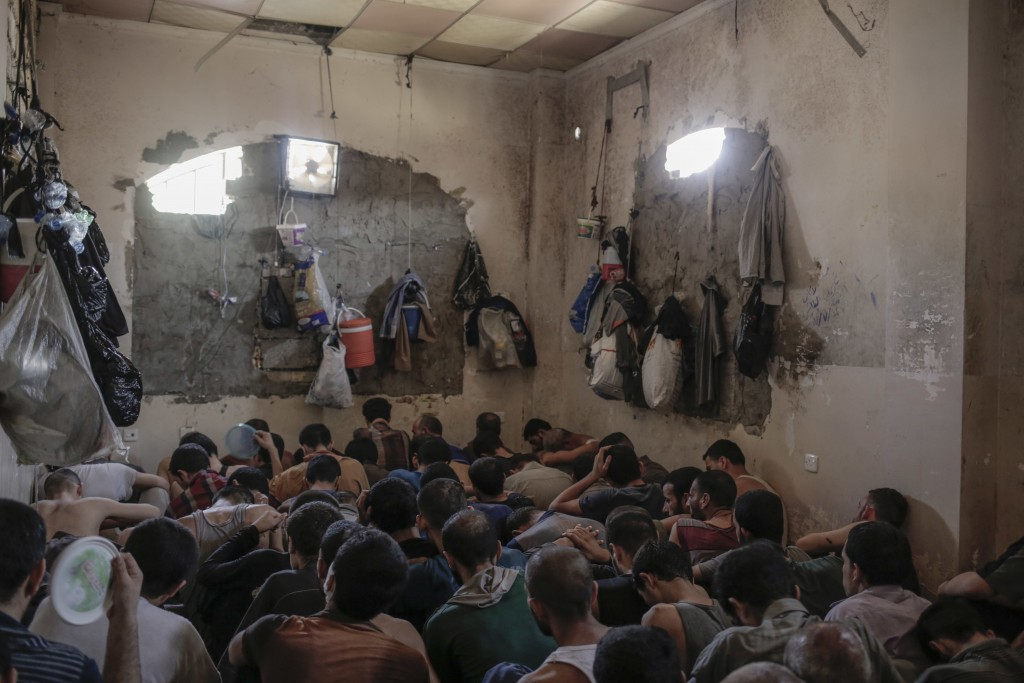 More than 100 Islamic State suspects sit inside a small room in a prison south of Mosul, Tuesday, July 18, 2017. A total of more 370 IS suspects are b...