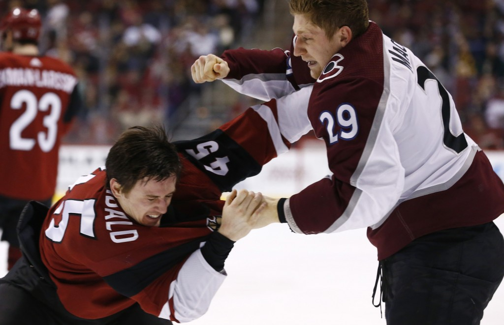 Colorado Avalanche center Nathan MacKinnon (29) tries to land a punch on Arizona Coyotes right wing Josh Archibald (45) as the two fight during the se...