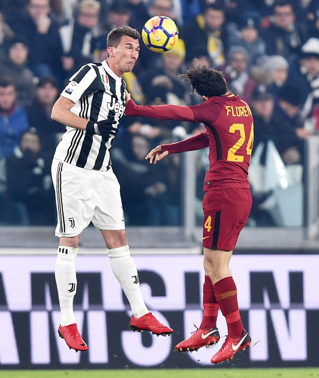 Juventus' Mario Mandzukic, left, and Roma's Alessandro Florenzi vie for the ball during the Italian Serie A soccer match between Juventus and Roma in ...