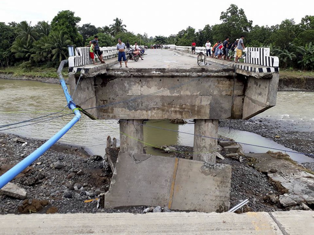 In this Dec. 24, 2017, file photo, people gather on a bridge which was washed out by flooding brought about by tropical storm Tembin in Zamboanga Del ...