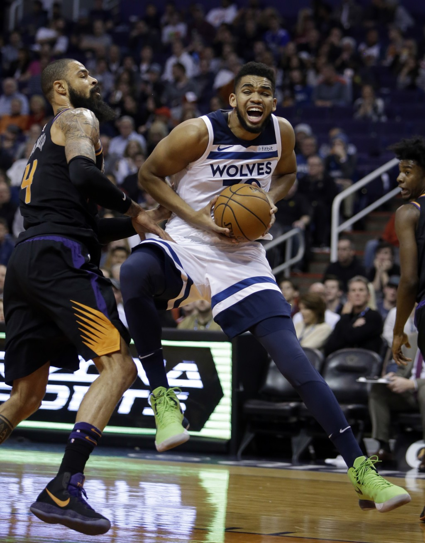 Minnesota Timberwolves center Karl-Anthony Towns (32) drives against Phoenix Suns center Tyson Chandler in the first quarter during an NBA basketball ...