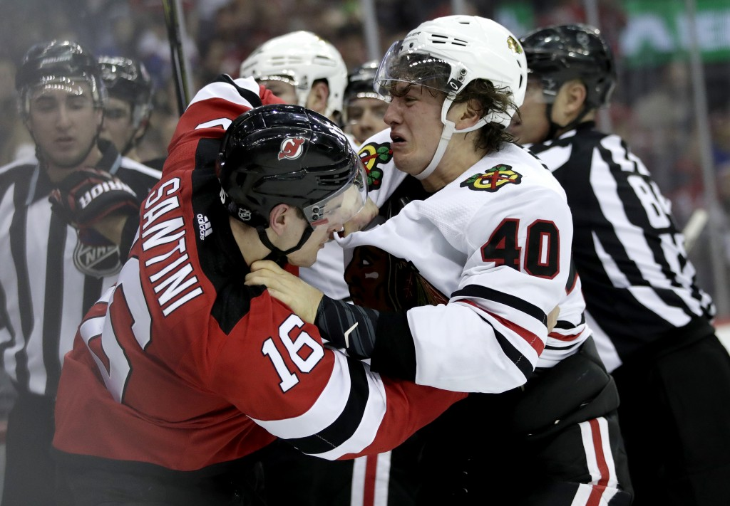 New Jersey Devils defenseman Steven Santini (16) and Chicago Blackhawks right wing John Hayden (40) fight during the first period of an NHL hockey gam...