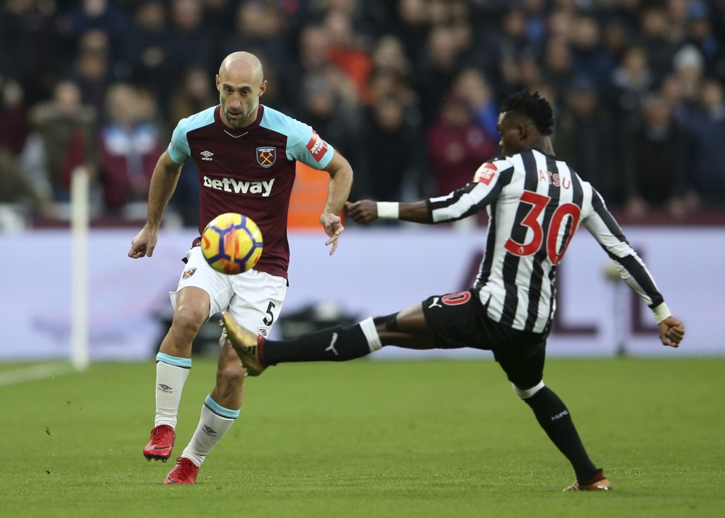West Ham United's Pablo Zabaleta, left, and Newcastle United's Christian Atsu battle for the ball during the English Premier League soccer match at th...