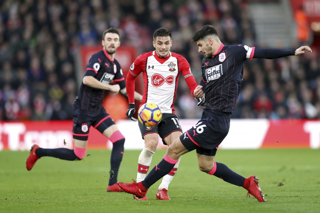 Southampton's Dusan Tadic, centre and Huddersfield Town's Christopher Schindler battle for the ball, during the English Premier League soccer match be...