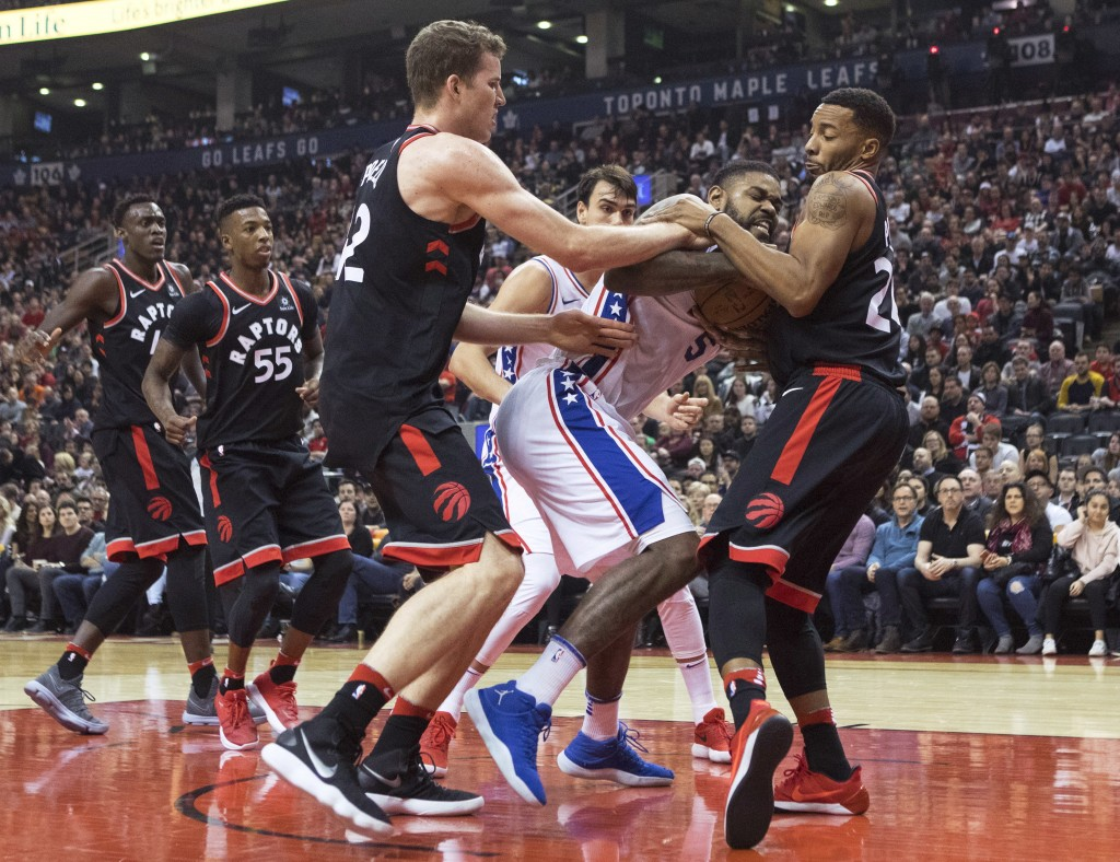 Philadelphia 76ers forward Amir Johnson, center, wrestles for the ball with Toronto Raptors' Norman Powell, right, and Jakob Poeltl during the first h...
