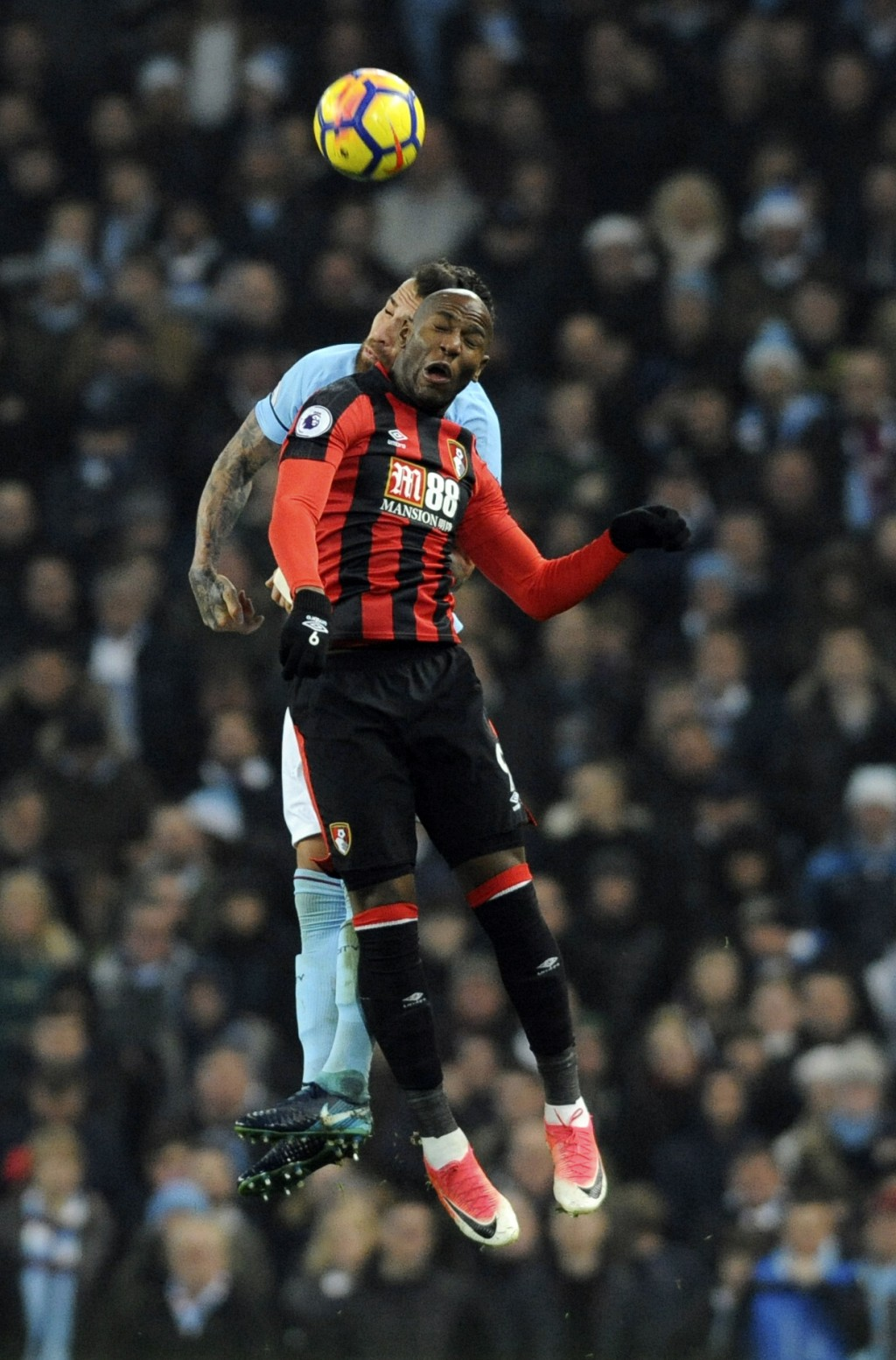 Manchester City's Nicolas Otamendi, behind, and Bournemouth's Benik Afobe battle for the ball during the English Premier League soccer match between M...