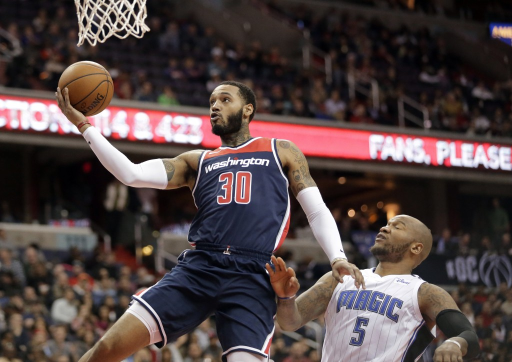 Washington Wizards forward Mike Scott (30) drives to the basket past Orlando Magic forward Marreese Speights (5) during the second half of an NBA bask...
