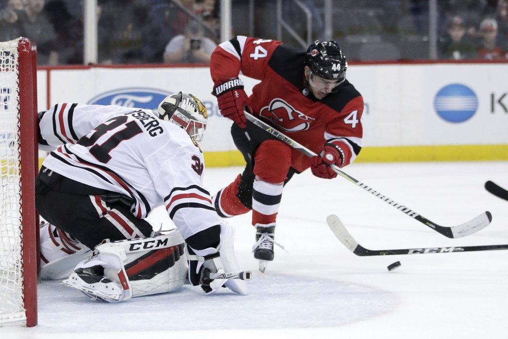 New Jersey Devils left wing Miles Wood (44) attacks as Chicago Blackhawks goalie Anton Forsberg (31), of Sweden, defends his net during the second per...
