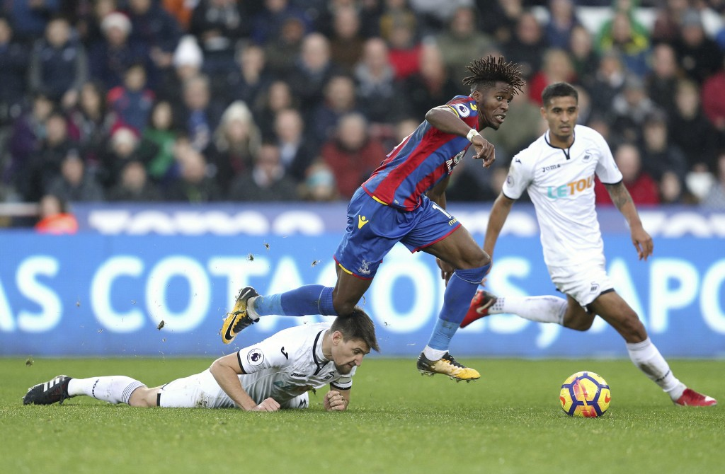 Swansea City's Federico Fernandez, left, and Crystal Palace's Wilfried Zaha battle for the ball during the English Premier League soccer match at the ...