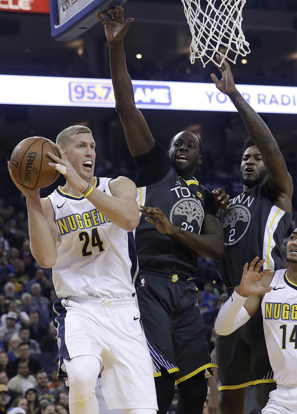 Denver Nuggets center Mason Plumlee (24) looks to pass the ball as Golden State Warriors forward Draymond Green, center, and forward Jordan Bell (2) d...