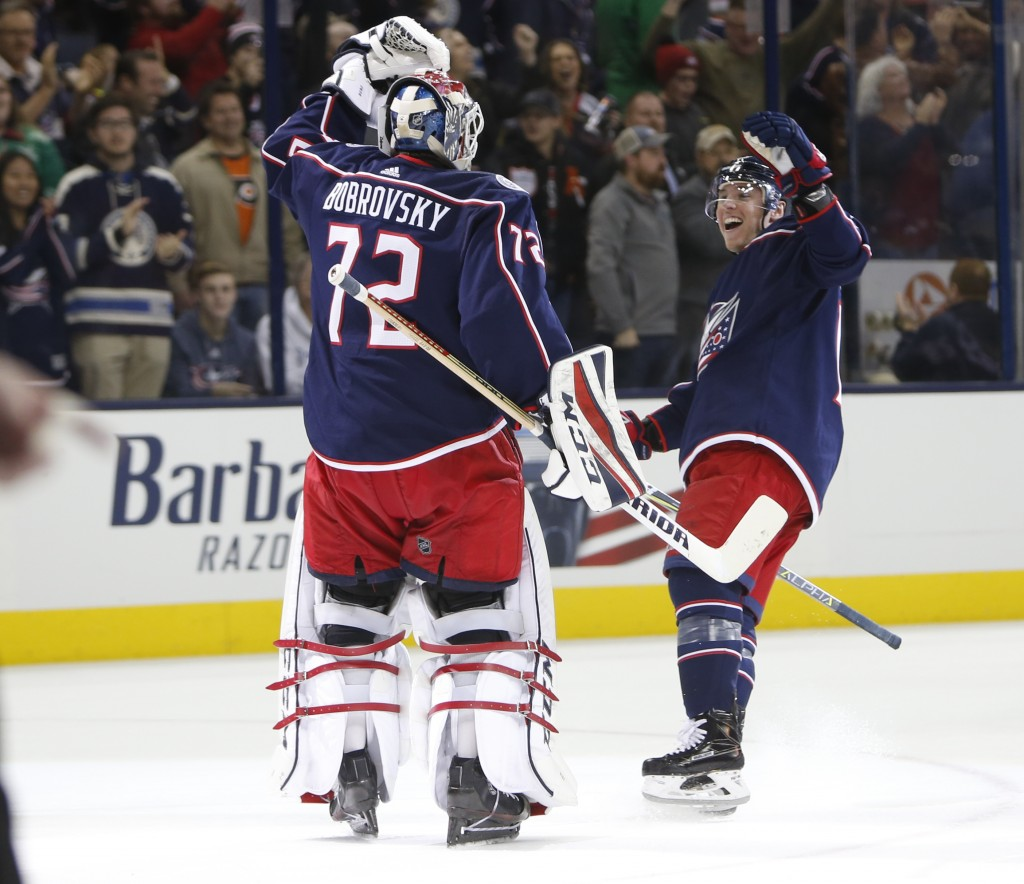 Columbus Blue Jackets' Sergei Bobrovsky, left, of Russia, and Cam Atkinson celebrate their win over the Philadelphia Flyers after the shootout period ...