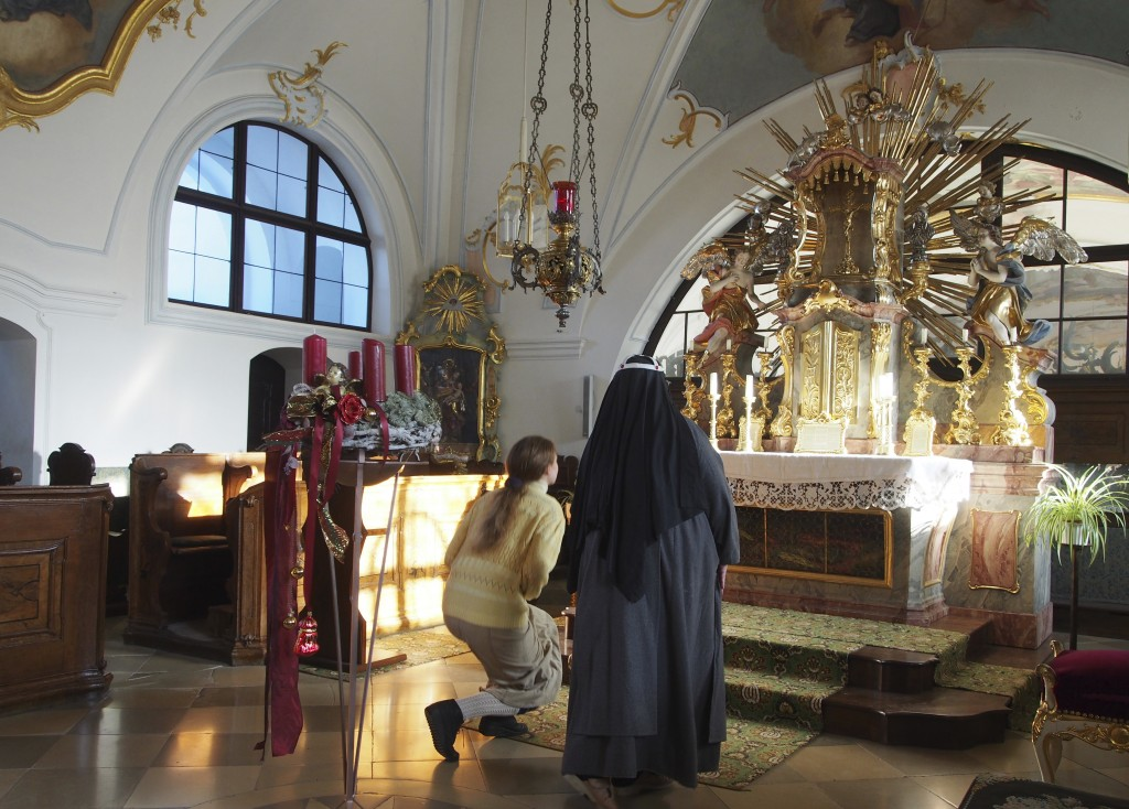 FILE -  In this Dec. 6, 2016 photo Sister Apollonia, right, and Postulant Claudia Schwarz kneel in front of the altar of the chapel of the abbey in Al...