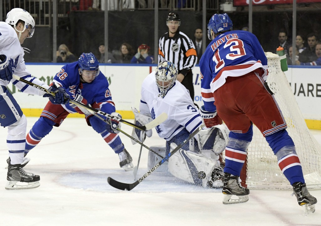Toronto Maple Leafs goalie Frederik Andersen (31) stops the puck as he is pressured by New York Rangers center Kevin Hayes (13) and left wing Jimmy Ve...