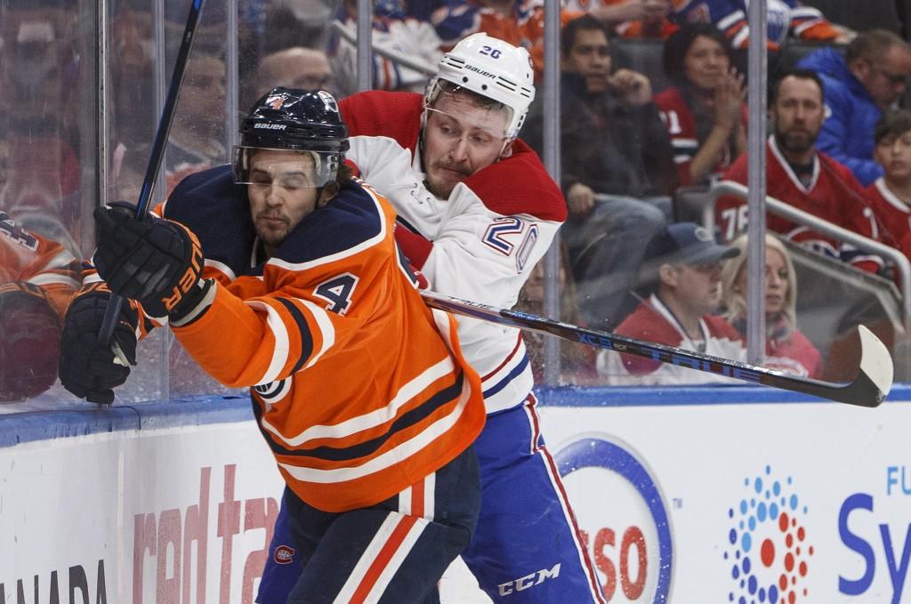 Montreal Canadiens Nicolas Deslauriers (20) checks Edmonton Oilers' Kris Russell (4) during first-period NHL hockey game action in Edmonton, Alberta, ...