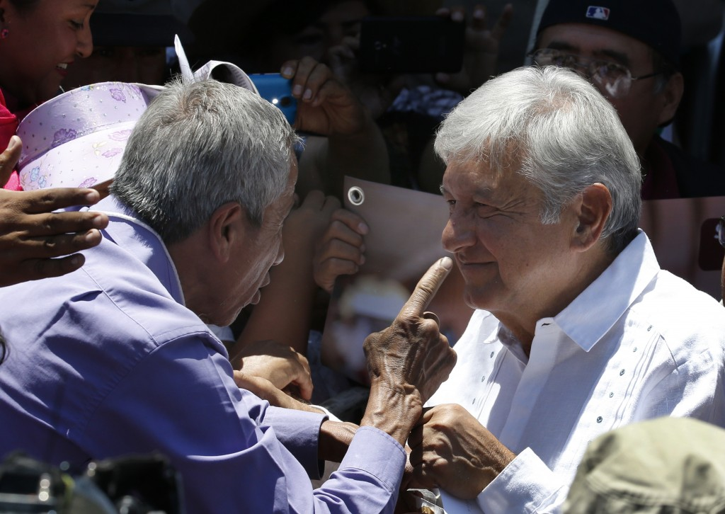 In this Sunday, April 30, 2017 photo, presidential hopeful Andres Manuel Lopez Obrador speaks with a supporter during a campaign rally in Atizapan de ...
